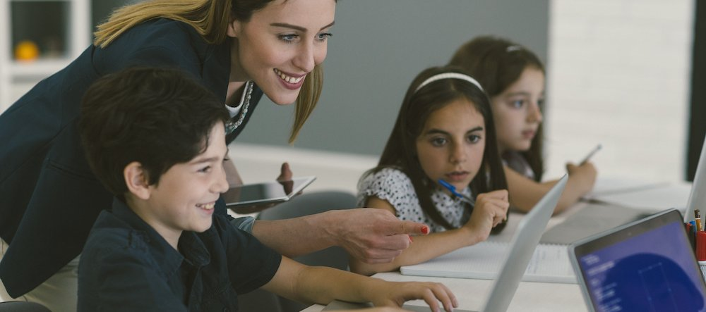 Kids at coding class. They are sitting by the desk and using laptop, coding. Selective focus on female teacher helping to male student with code.